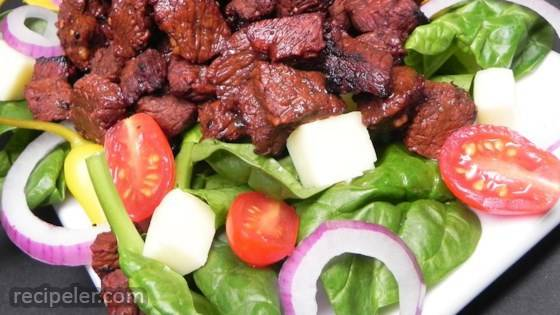 Churrasco on a Bed of Baby Spinach Tossed in Lime Dressing